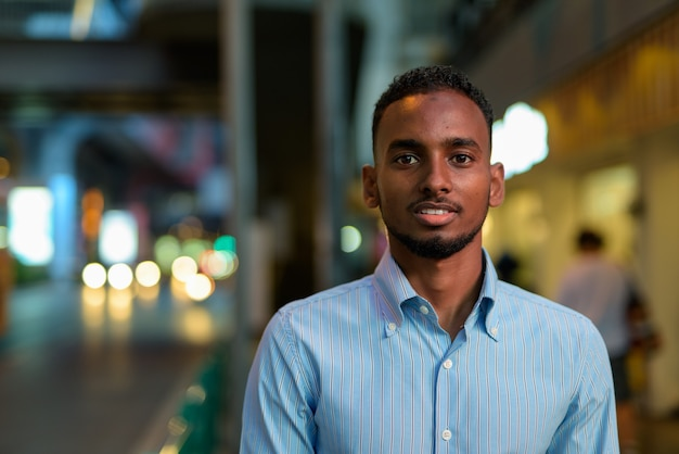 Portrait of handsome black african businessman outdoors in city at night smiling horizontal shot