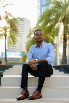 Portrait of handsome black african businessman sitting outdoors in city during summer while thinking vertical shot