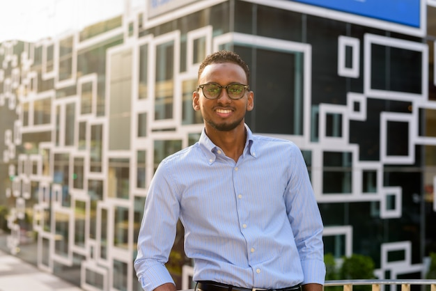 Portrait of handsome black african businessman smiling outdoors in city during summer