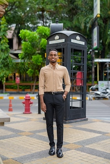 Portrait of handsome black young african businessman wearing casual clothes outdoors in city