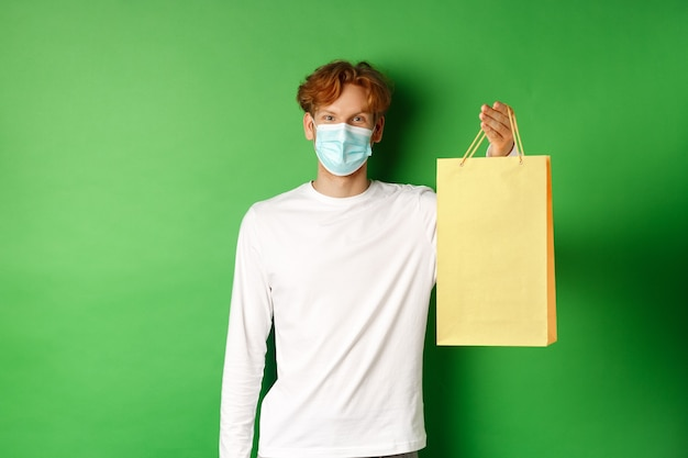 Portrait of handsome boyfriend in face mask giving shopping bag with valentines gift, smiling with eyes, standing over green background.