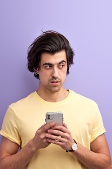 Portrait of handsome brunette man with smartphone chatting with friend, isolated on purple studio background