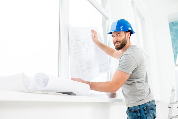 Portrait of a handsome builder, foreman or repairman in the helmet looking at the paper drawings near the window indoors