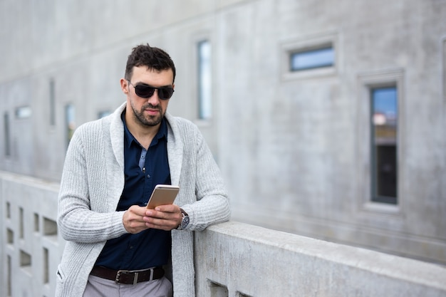 Portrait of handsome business man with smart phone posing over modern building