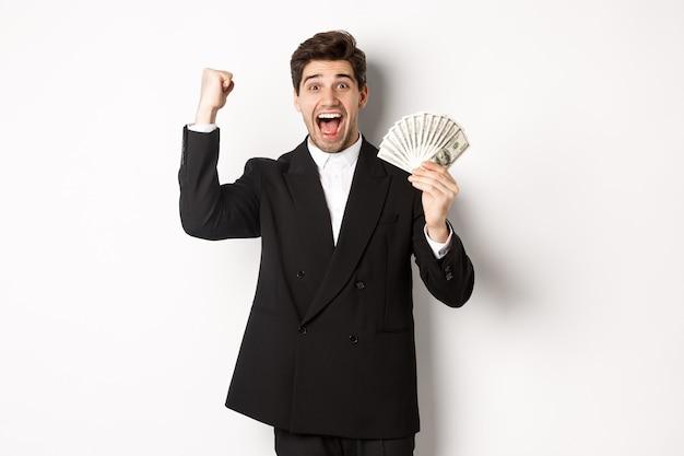 Ritratto di un bell'uomo d'affari in abito nero, che vince denaro e si rallegra, alzando la mano con eccitazione, in piedi su sfondo bianco.