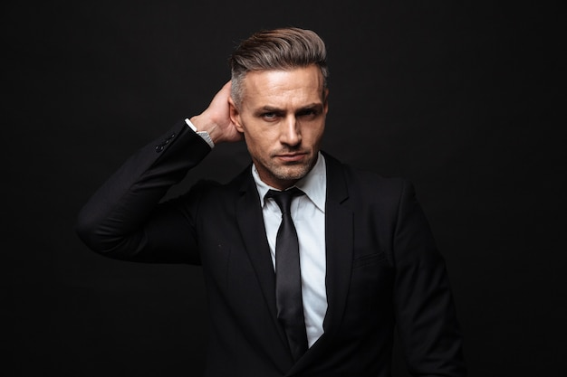 Portrait of handsome businessman dressed in formal suit posing and looking at camera isolated over black wall