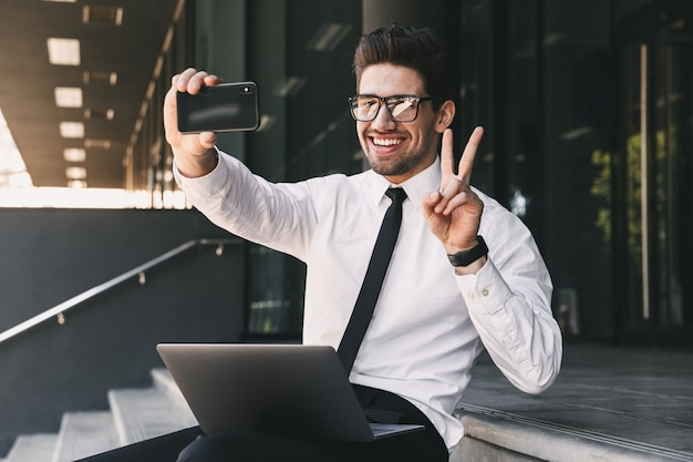 Portrait of handsome businessman dressed in formal suit sitting outside glass building with laptop, and taking selfie photo on smartphone