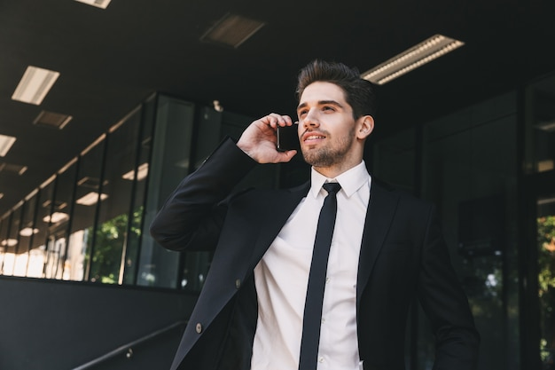 Portrait of handsome businessman dressed in formal suit standing outside glass building, and speaking on mobile phone