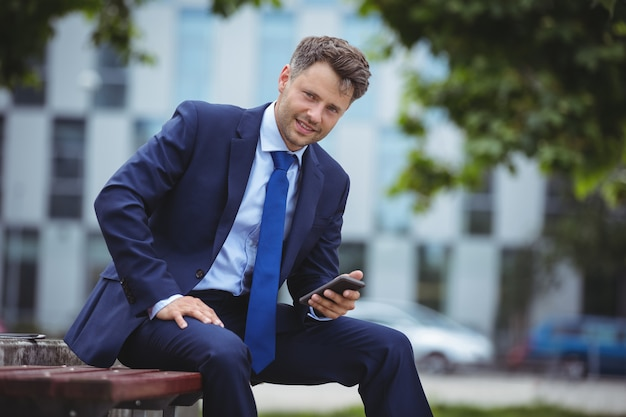 Portrait of handsome businessman holding mobile phone