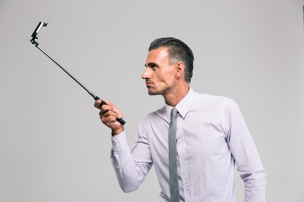 Portrait of a handsome businessman holding selfie stick isolated