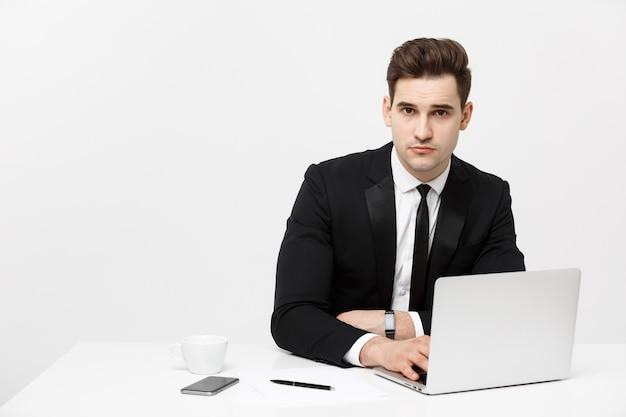 Ritratto di un bell'uomo d'affari che tiene in mano uno smartphone mentre lavora su un computer alla sua scrivania è ...