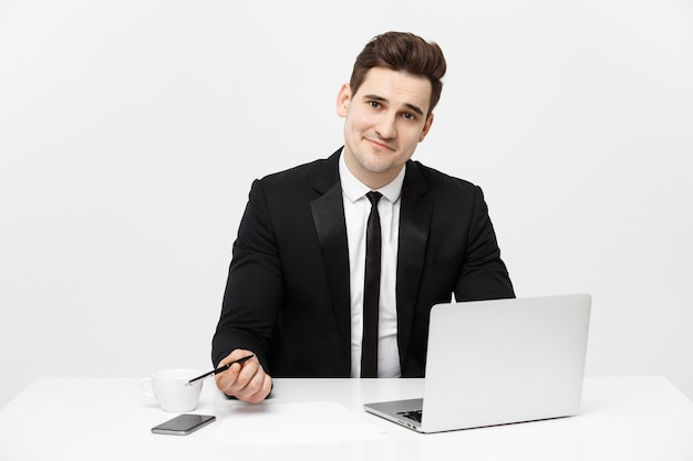 Portrait of a handsome businessman holding smartphone while working on a computer at his desk he is ...