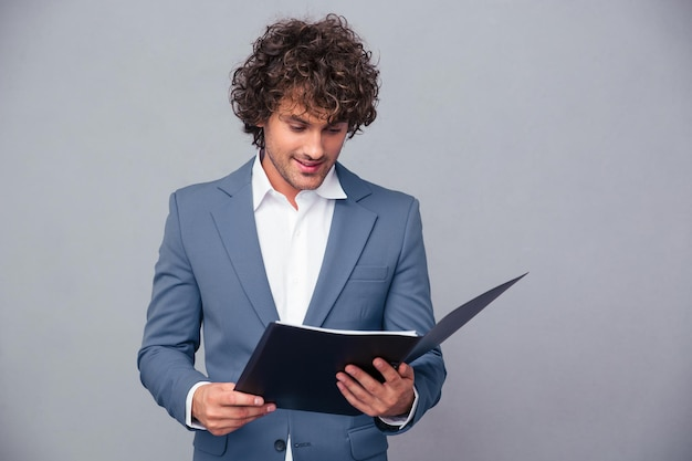 Portrait of a handsome businessman reading documents in folder over gray wall