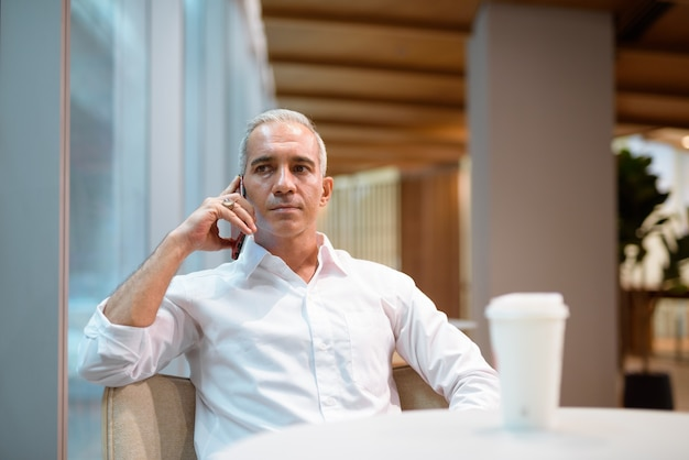 Portrait of handsome businessman sitting at coffee shop and talking on mobile phone