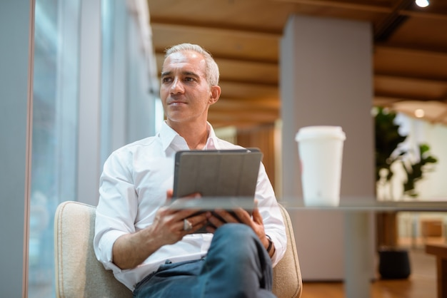 Portrait of handsome businessman sitting at coffee shop and using digital tablet while looking through window and thinking horizontal shot