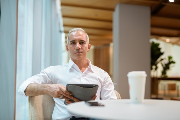 Portrait of handsome businessman sitting at coffee shop and using digital tablet
