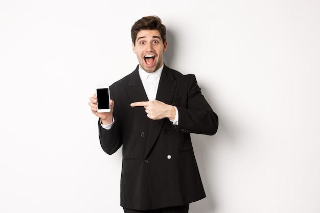 Ritratto di uomo d'affari bello in tuta, puntando il dito sullo schermo del telefono cellulare, mostrando pubblicità, in piedi su sfondo bianco.