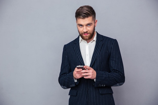 Portrait of a handsome businessman using smartphone over gray wall and looking at camera