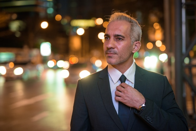 Portrait of handsome businessman wearing suit in city at night while thinking