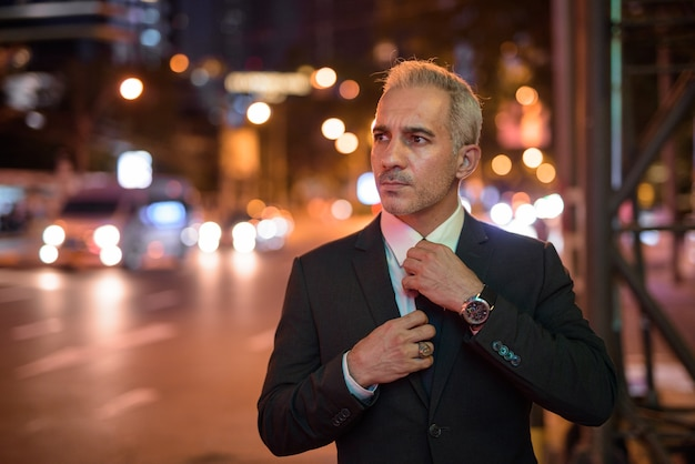 Portrait of handsome businessman wearing suit in city at night