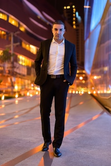 Portrait of handsome businessman wearing suit outdoors at night in city