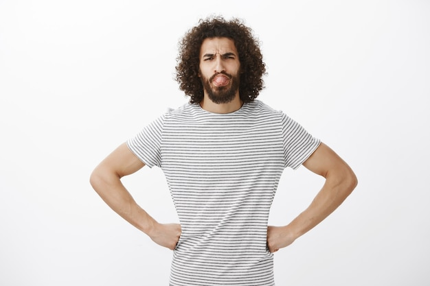 Portrait of handsome carefree bearded boyfriend in stylish t-shirt, holding hands on hips with confident expression, frowning and sticking out tongue