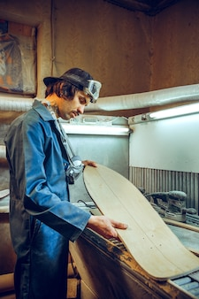 Portrait of handsome carpenter working with wooden skate at workshop, profile view