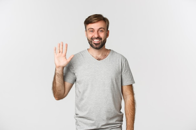Portrait of handsome caucasian man in gray t-shirt, saying hello and friendly waving hand, standing