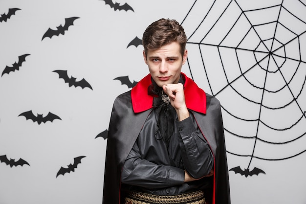 Portrait of handsome caucasian vampire in black and red halloween costume.