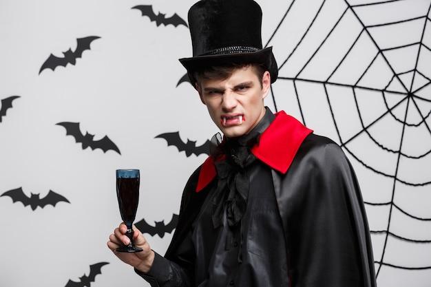 Portrait of handsome caucasian vampire enjoy drinking bloody red wine.