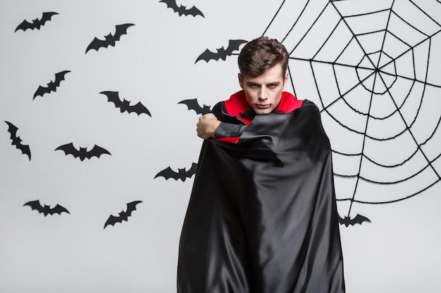 Portrait of handsome caucasian vampire halloween costume fluttering his red, black cloak.