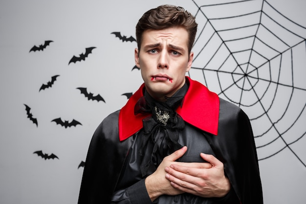 Portrait of handsome caucasian in vampire halloween costume holding hand on heart.