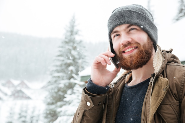 Portrait of handsome cheerful bearded man samiling and talking on mobile phone outdoors in winter