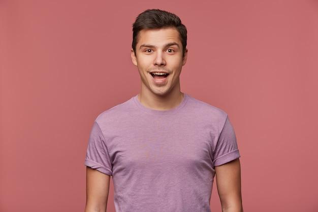Ritratto di bel ragazzo allegro indossa in maglietta vuota, guarda la telecamera con felice espressione stupita, si erge su sfondo rosa. Foto Gratuite
