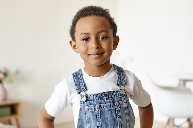 Portrait of handsome cheerful little boy of african origin posing indoors