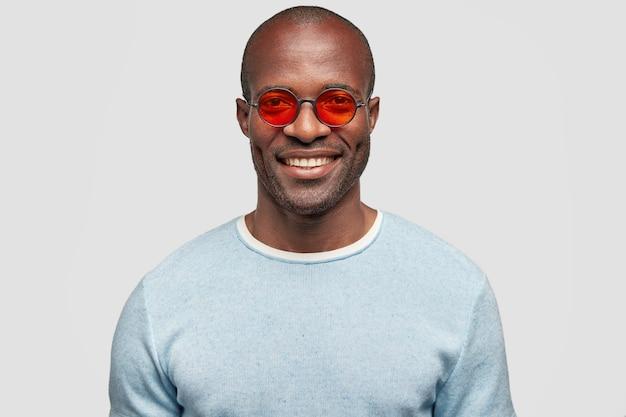 Ritratto del manager maschio allegro bello in occhiali da sole rossi alla moda