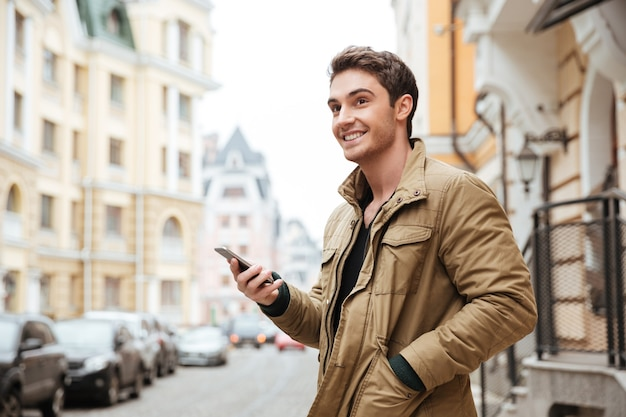 Portrait of handsome cheerful man walking on street and chatting by his phone outdoors. look aside.