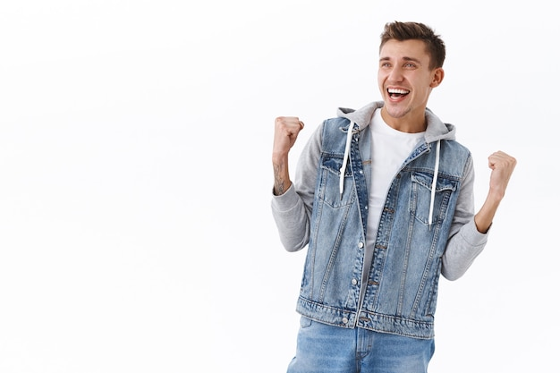 Portrait of handsome cheerful, triumphing blond man in denim jacket, fist pump achieve goal, looking at tv screen at pub as watching sports game winning bet, become champion, celebrating victory