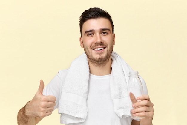 Portrait of handsome cheerful young unshaven man with confident broad smile making thumbs up gesture refreshing himself after training at gym