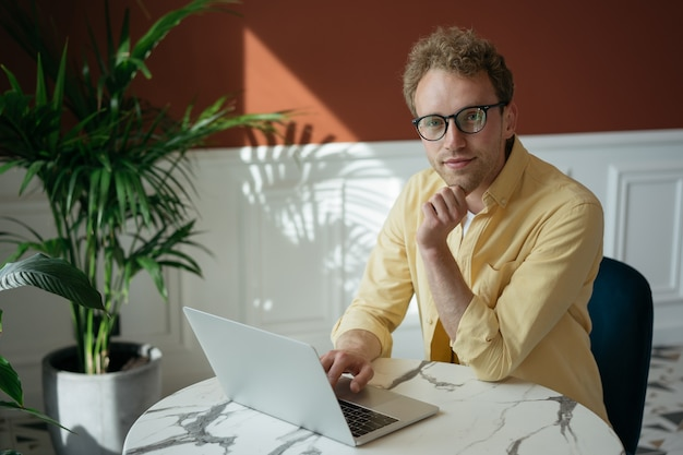 Portrait of handsome computer programmer wearing eyeglasses using laptop computer working from home