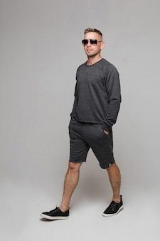 Portrait of handsome confident blond caucasian man in sunglasses wearing grey pullover and bermuda shorts walking with hands in pockets.