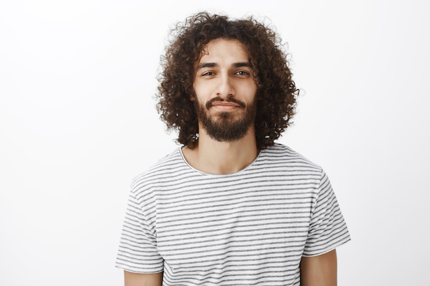 Portrait of handsome confident creative boyfriend with dark curly hair, standing with slight smile and self-assured expression