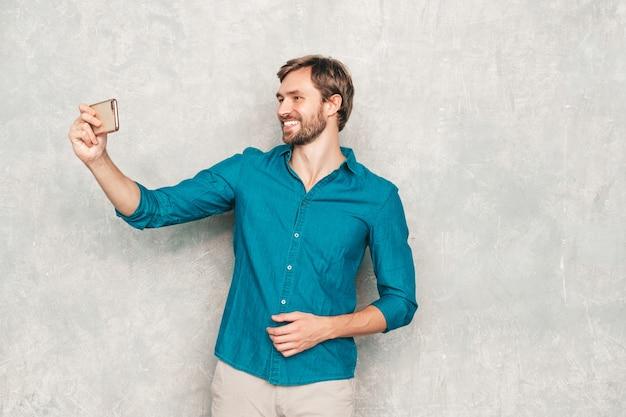 Ritratto del modello di uomo d'affari lumbersexual hipster fiducioso bello che indossa i vestiti casuali della camicia dei jeans.