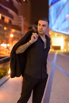 Portrait of handsome confident man with short hair outdoors at night in city