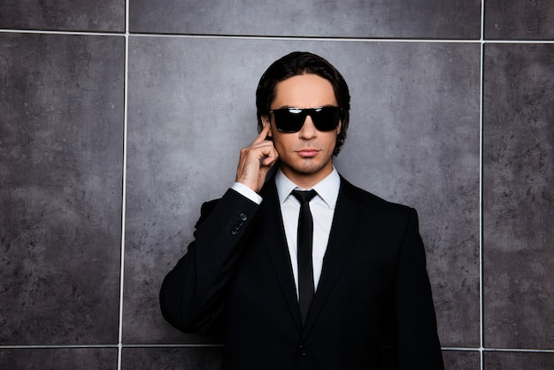 Portrait of handsome confident young businessman in black glasses