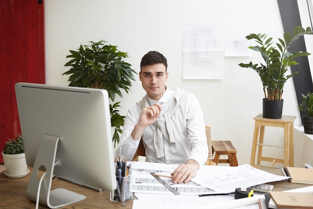 Portrait of handsome confident young male engineer making drawings of residential housing project or commercial building, sitting at his desk with blueprints, computer and engineering tools