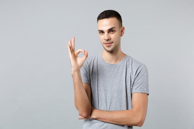 Ritratto di un bel giovane fiducioso in abiti casual in piedi, che mostra gesto ok ok