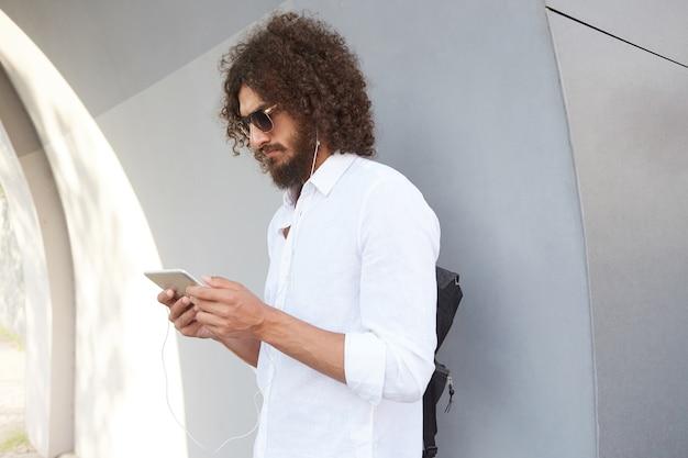 Ritratto di bell'uomo riccio dai capelli scuri con occhiali da sole in posa sopra la parete esterna grigia, tenendo il tablet in mano e guardando seriamente sullo schermo