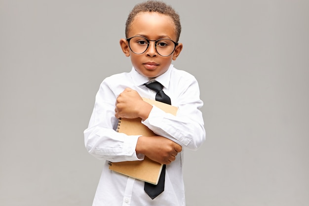 Portrait of handsome dark skinned schoolboy with short afro haircut posing isolated in glasses, shirt and tie embracing copybook, feeling shy in new school. learning and knowledge