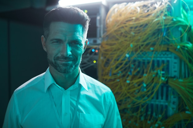 Portrait of handsome data engineer smiling at camera in server room while working with supercomputer in blue light, copy space